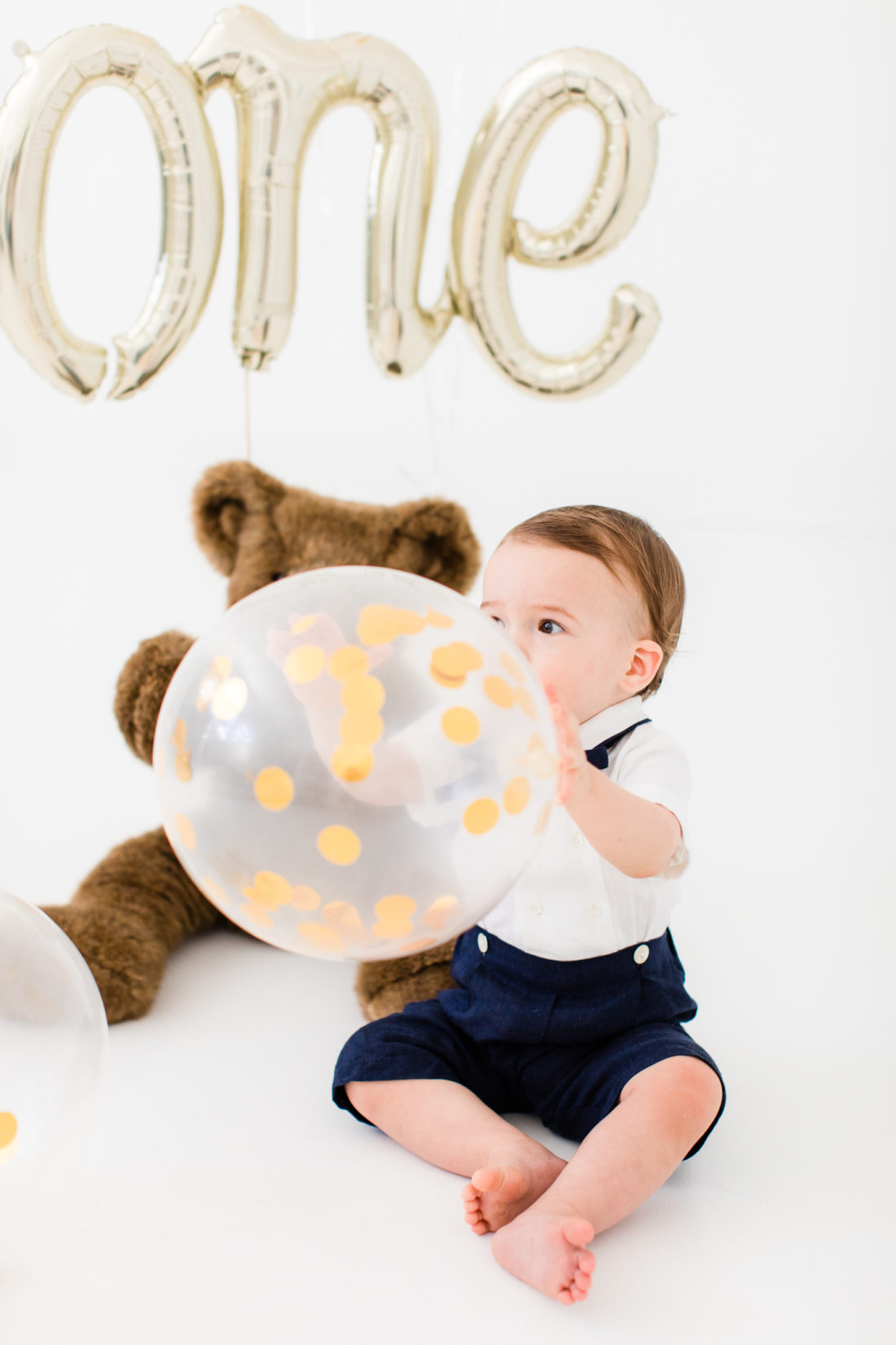 Major Martino holds a gold confetti filled balloon to celebrate his first birthday