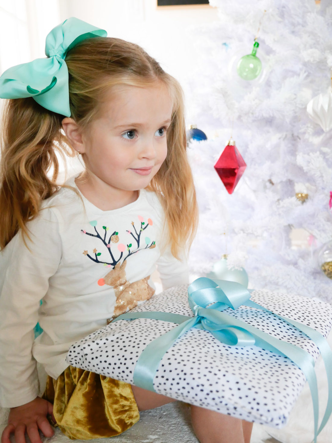 Marlowe Martino is pictured with a wrapped gift in the family room of her connecticut home