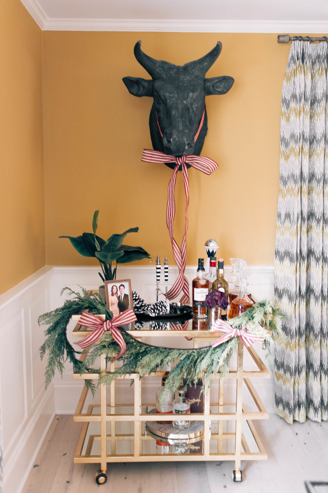 The bar cart in Eva Amurri Martino's connecticut home is dressed up for the holiday season with a garland and ribbon