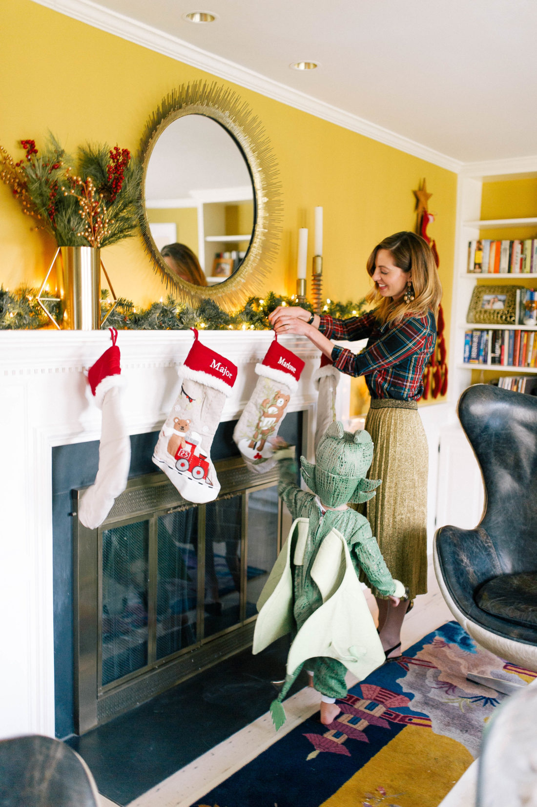 Eva Amurri Martino and three year old daughter Marlowe hang Christmas stocking on the mantel in their Connecticut home