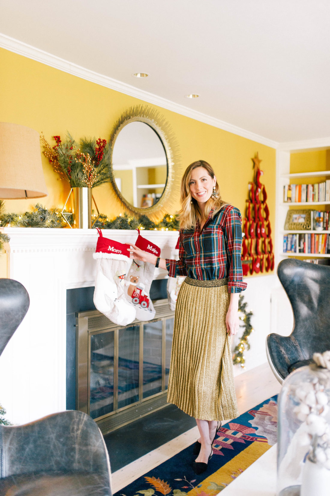 Eva Amurri Martino stands in front of the mantel in her living room that his hung with stockings for Christmas