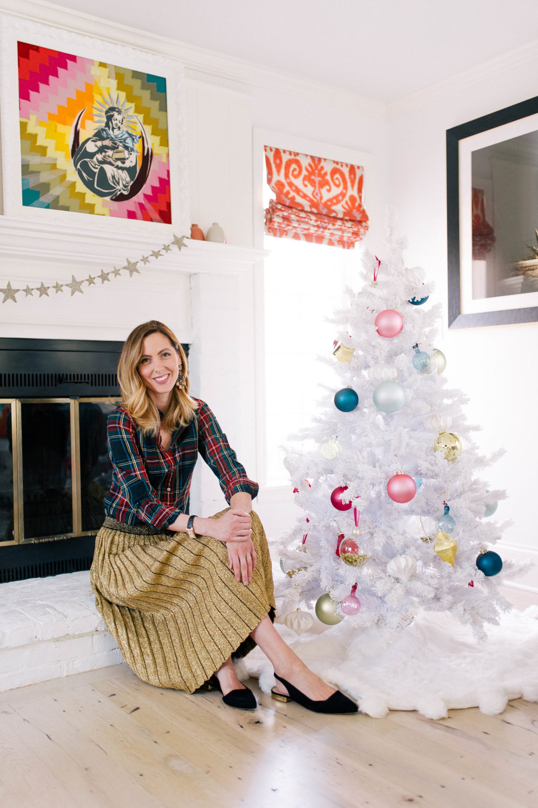 Eva Amurri Martino sits next to her white christmas tree decorated with colorful ornaments in the family room of her Connecticut home