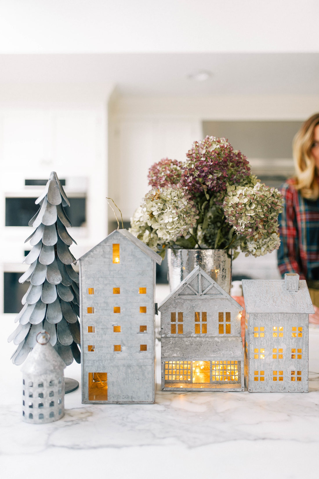 Eva Amurri Martino prepares lunch in her kitchen that is decorated for christmas with galvanized steel houses filled with twinkly lights
