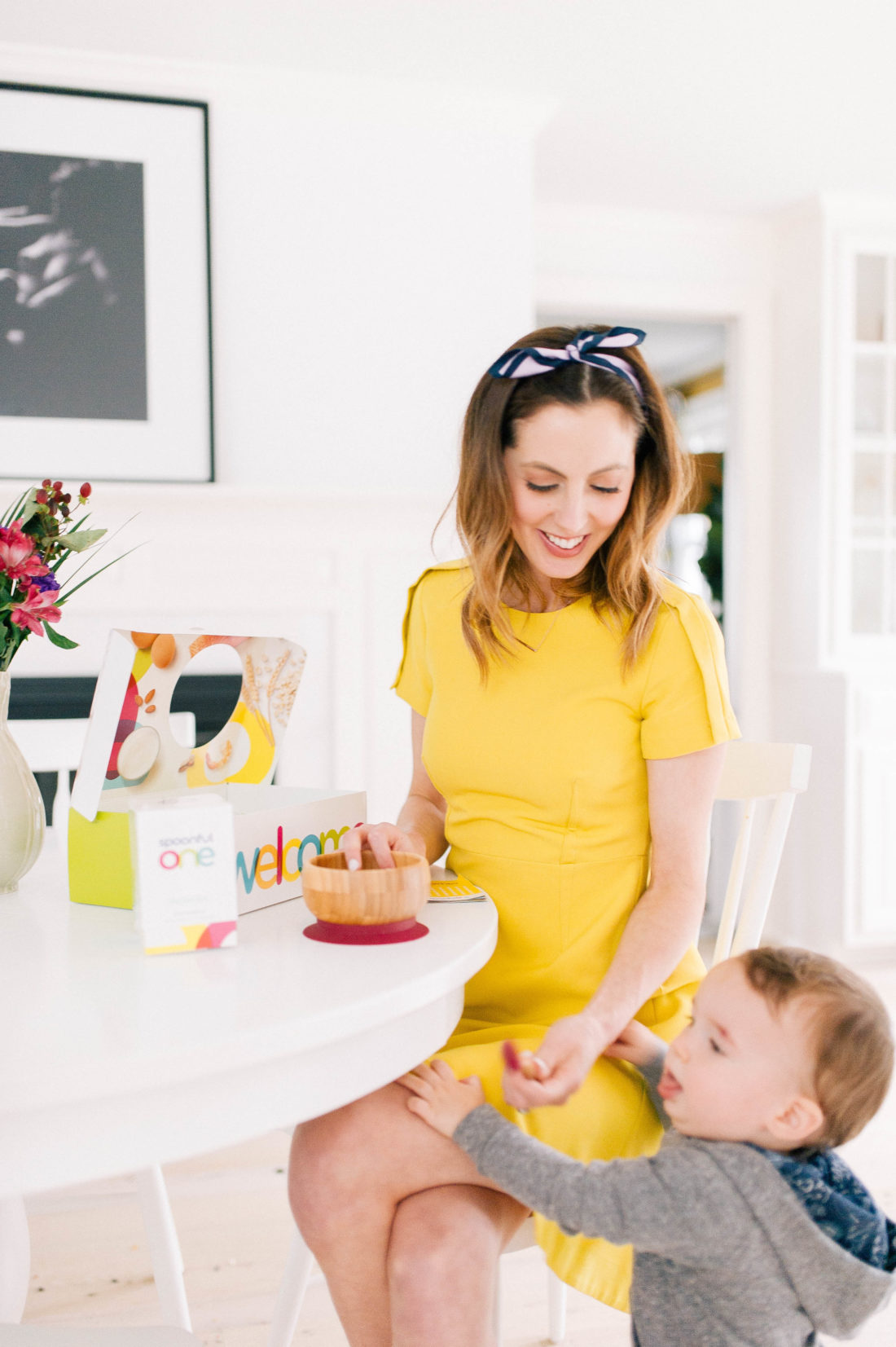 Eva Amurri Martino wears a yellow dress and sits in the kitchen of her Connecticut home as she feeds SpoonfulOne to her son Major