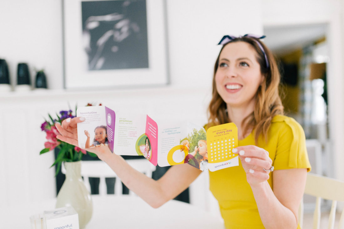 Eva Amurri Martino wears a yellow dress and reads the directions of SpoonfulOne mixins
