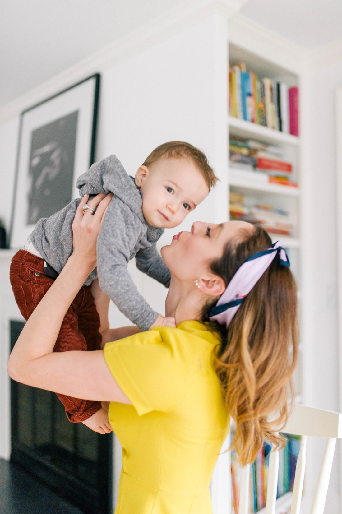 Eva Amurri Martino wears a yellow dress and lifts son Major up in her arms to kiss him