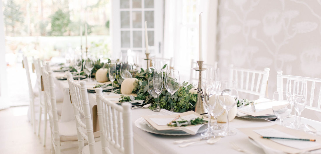 Crisp and modern white, flax, and silver tablescape at Eva Amurri Martino's Friendsgiving, featuring a long eucalyptus garland and white pumpkins