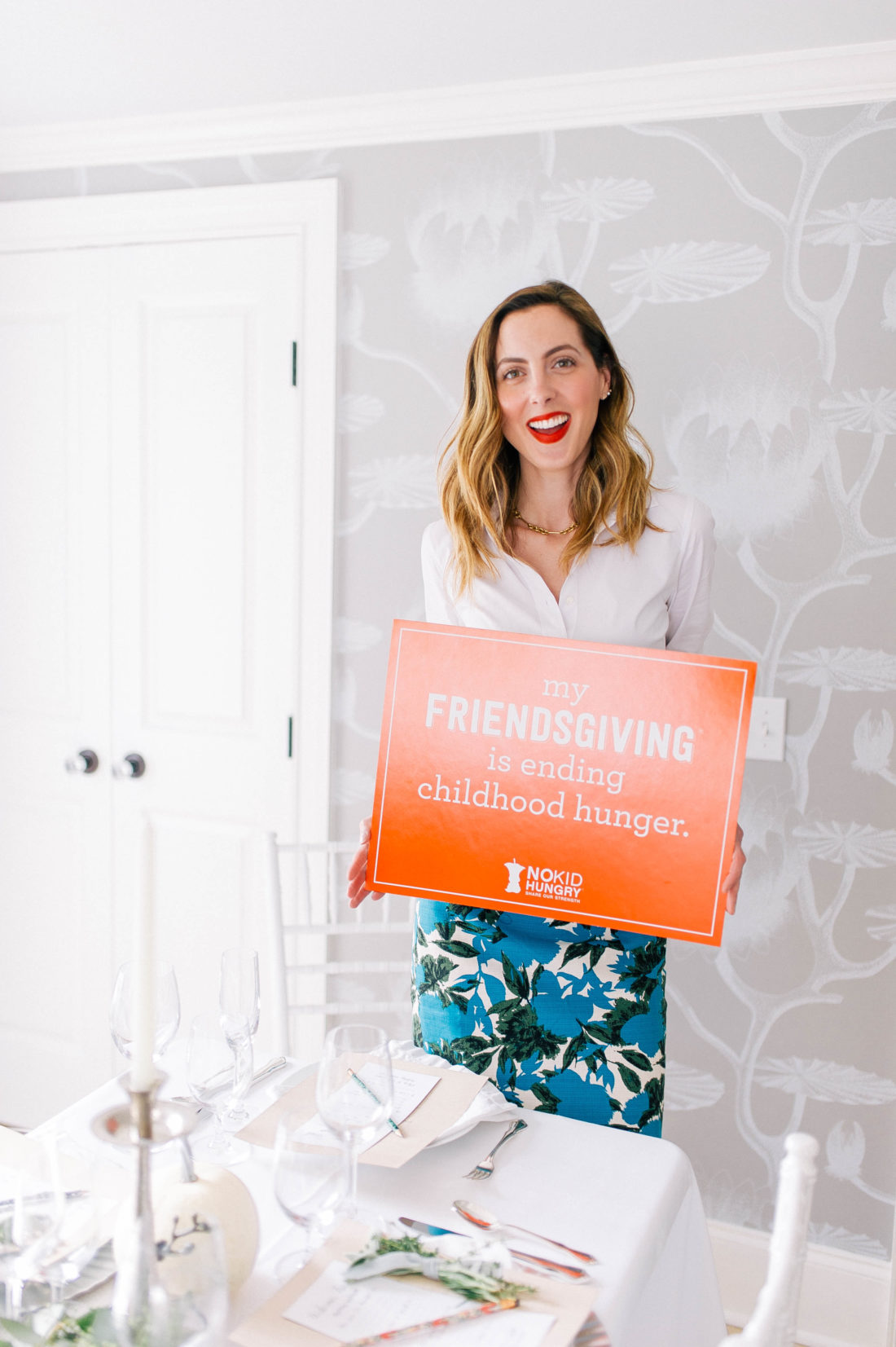 Eva Amurri Martino holds up a sign in the dining room of her connecticut home as part of her Friendsgiving event for No Kid Hungry