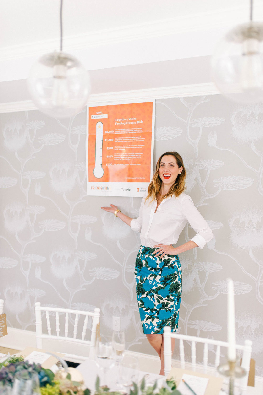 Eva Amurri Martino stands next to her fundraising goal at her Friendsgiving event for No Kid Hungry at her connecticut home