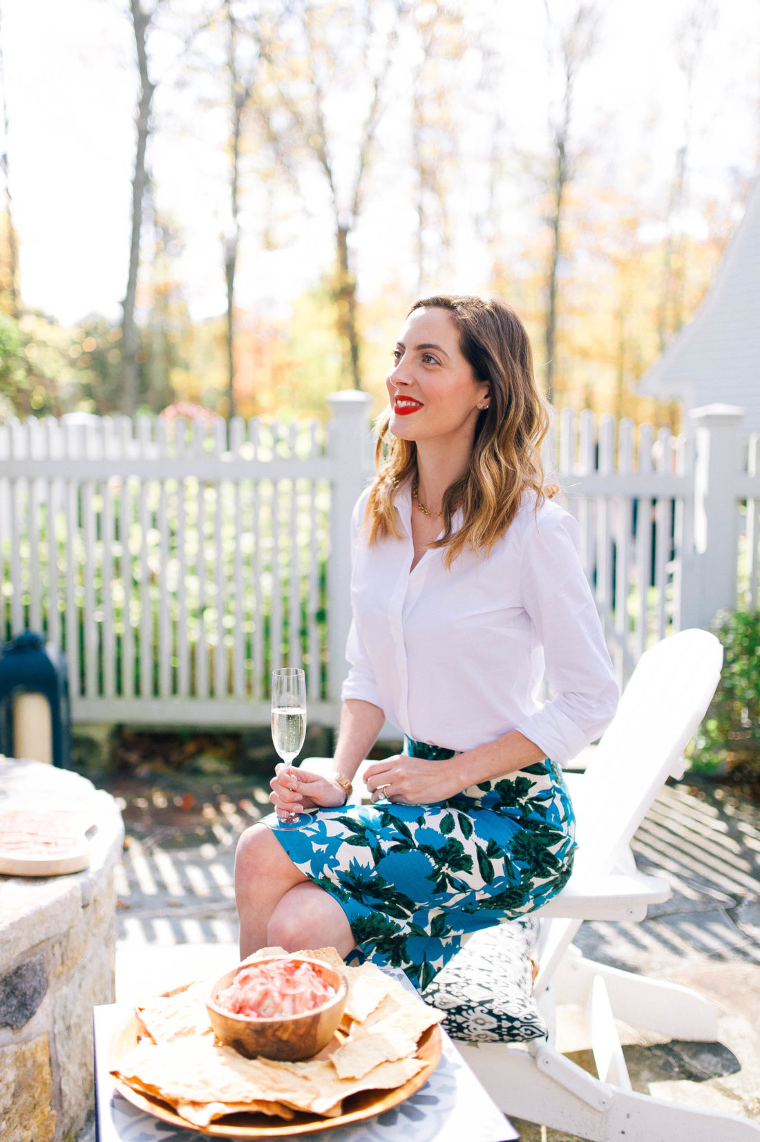Eva Amurri Martino sits beside the fire pit at a party at her home, holding a glass of champagne and wearing a floral pencil skirt and red lipstick