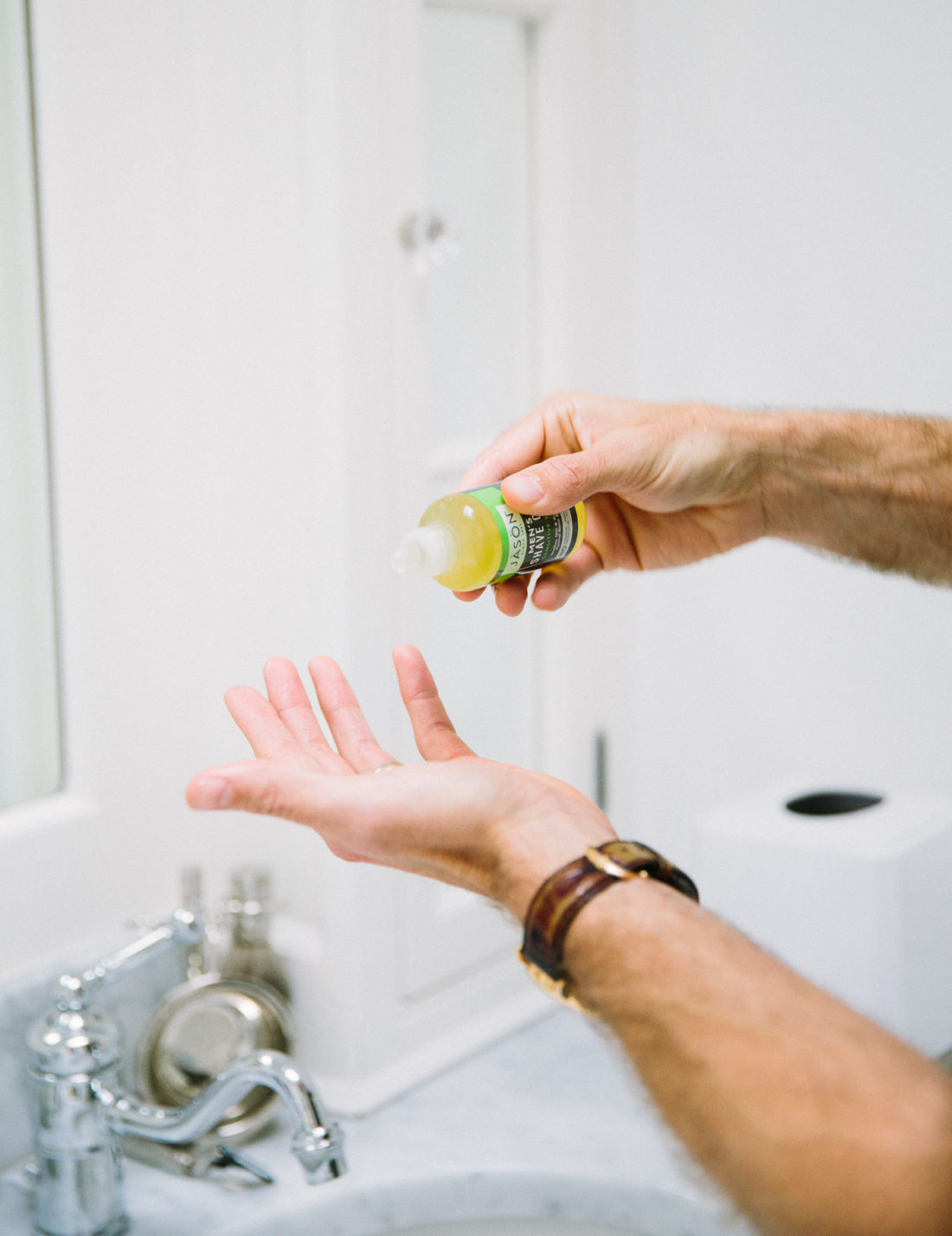 Kyle Martino uses shave oil to shave off his beard in the bathroom of his Connecticut home