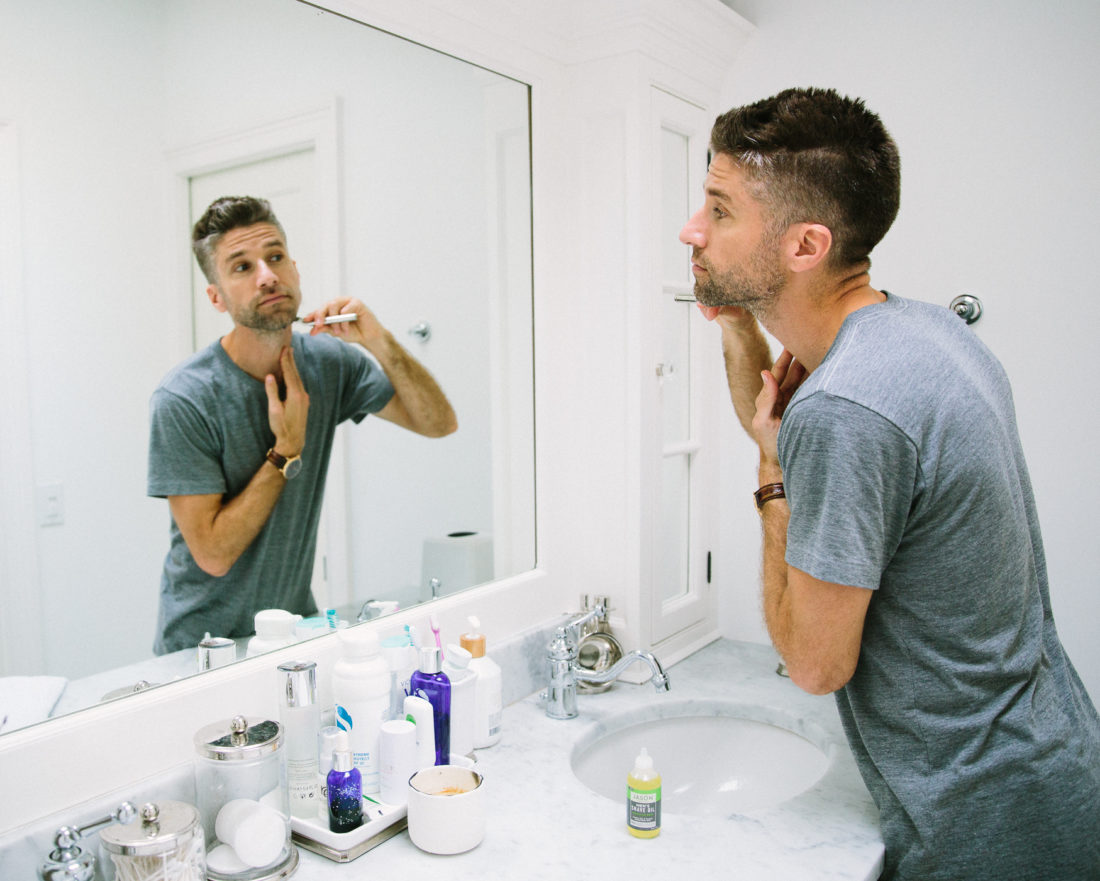 Kyle Martino wears a gray Tshirt and shaves his beard in the bathroom of his Connecticut home