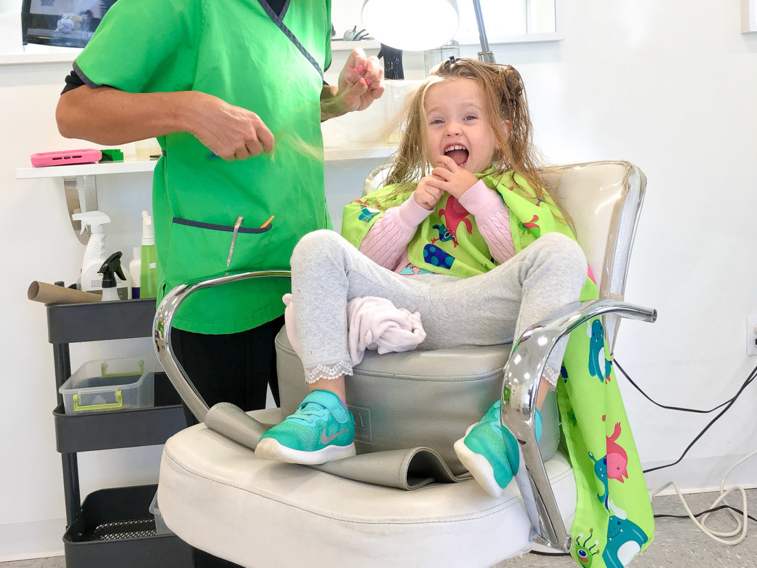 Marlowe Martino eats a lollipop while she gets her hair checked for lice