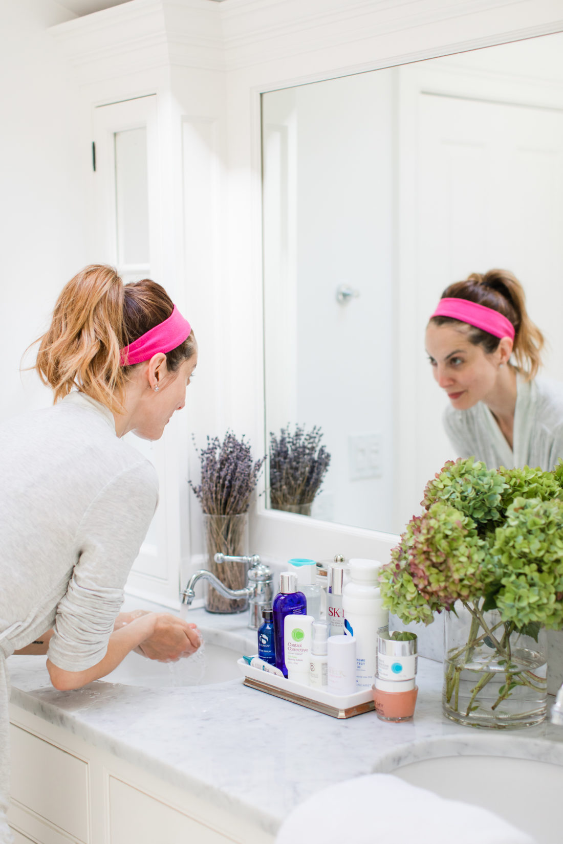 Eva Amurri Martino rinses off the face wash during her skin care routine in the bathroom of her Connecticut home