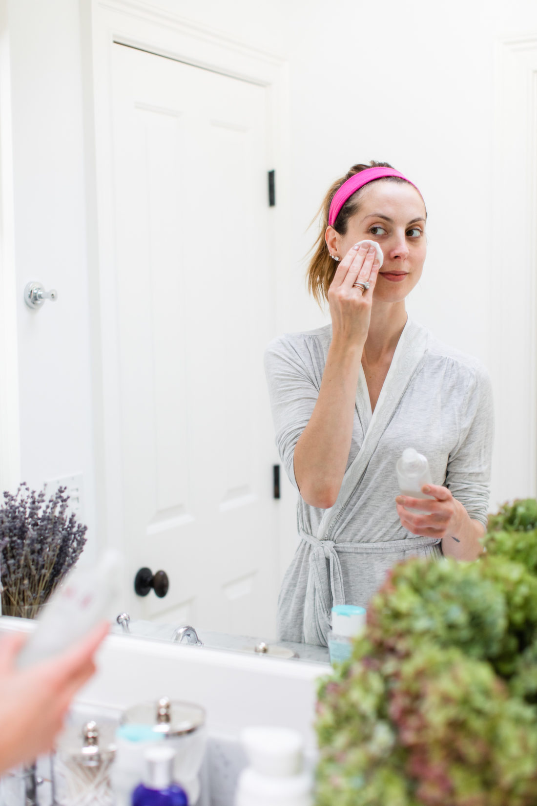 Eva Amurri Martino presses SKII facial treatment essence gently in to her skin using a cotton pad