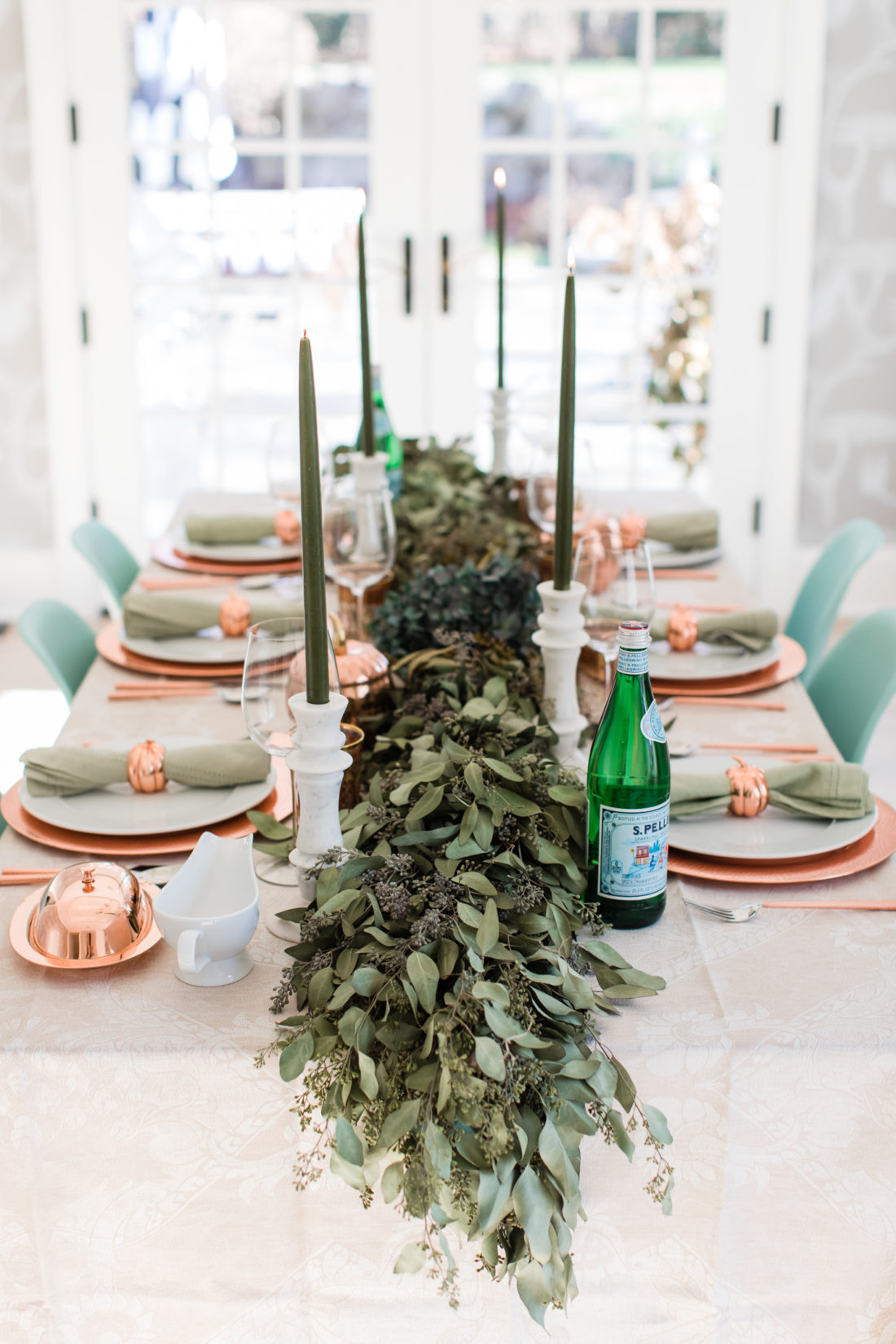 A eucaluptus garland, marble candlesticks with green candles, and a green and copper color scheme add style to Eva Amurri Martino's thanksgiving table