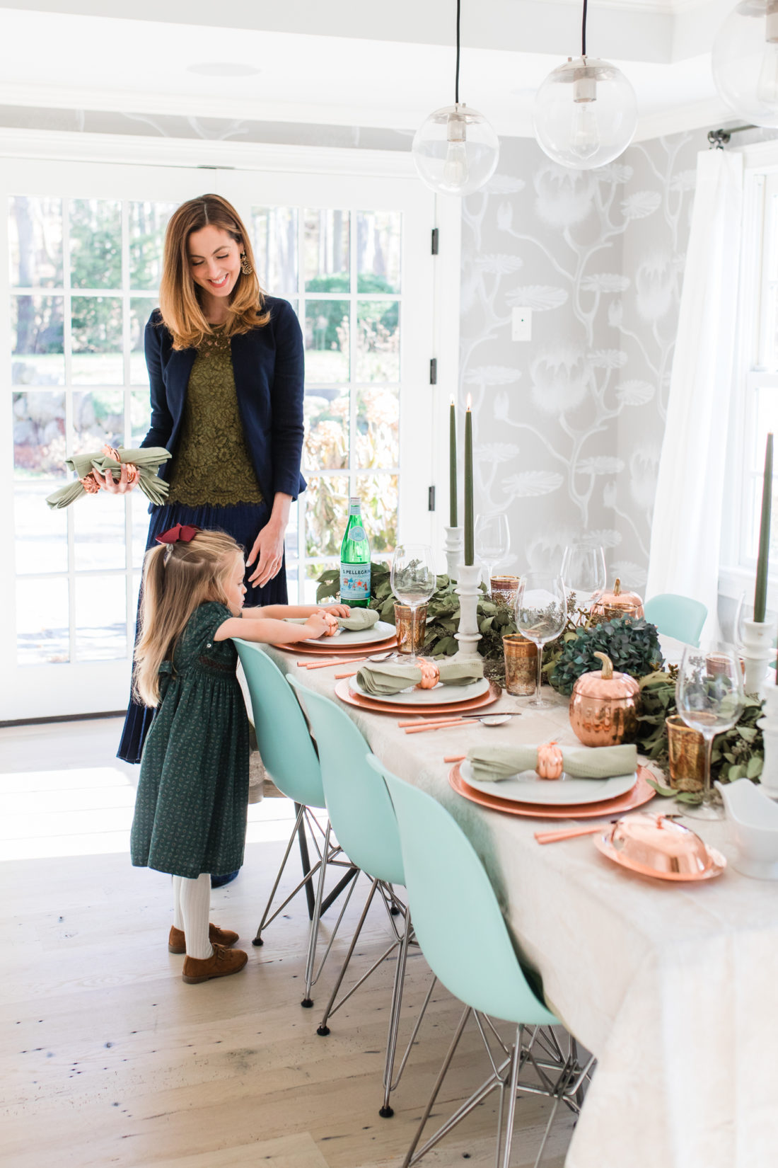 Marlowe Martino helps her Mom set the Thanksgiving table wearing a green velvet smocked party dress
