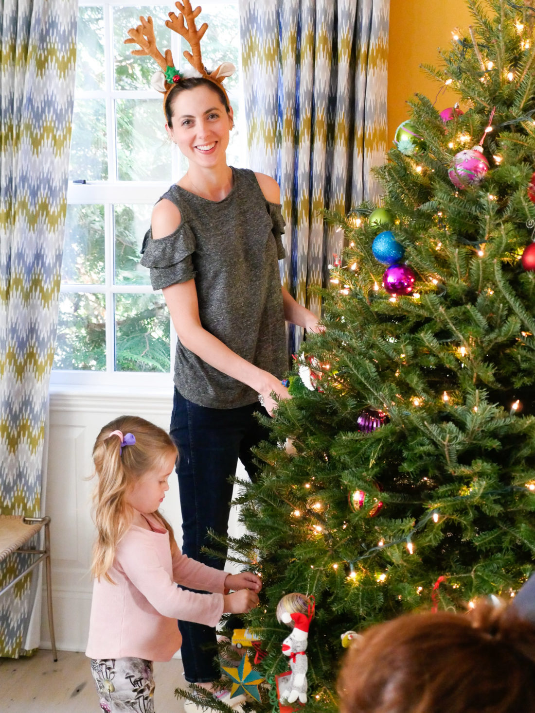Eva Amurri Martino wears reindeer antlers and decorates her Christmas tree with her family using a variety of ornaments collected over the years