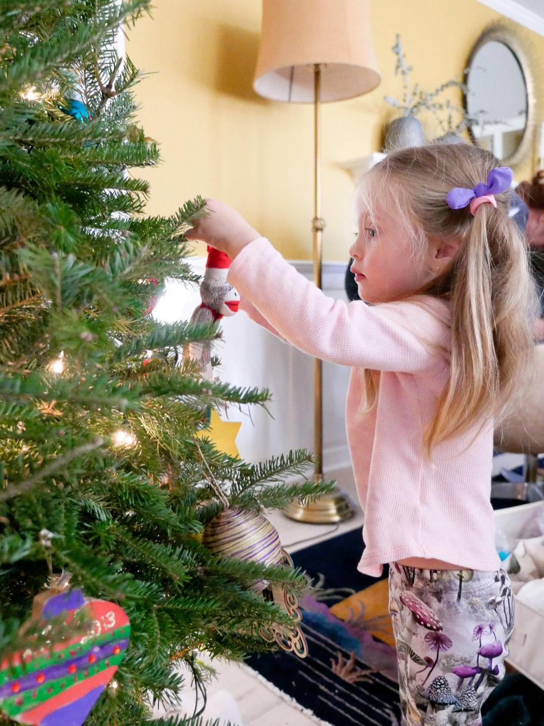 Marlowe Martino hangs an ornament on her family Christmas tree