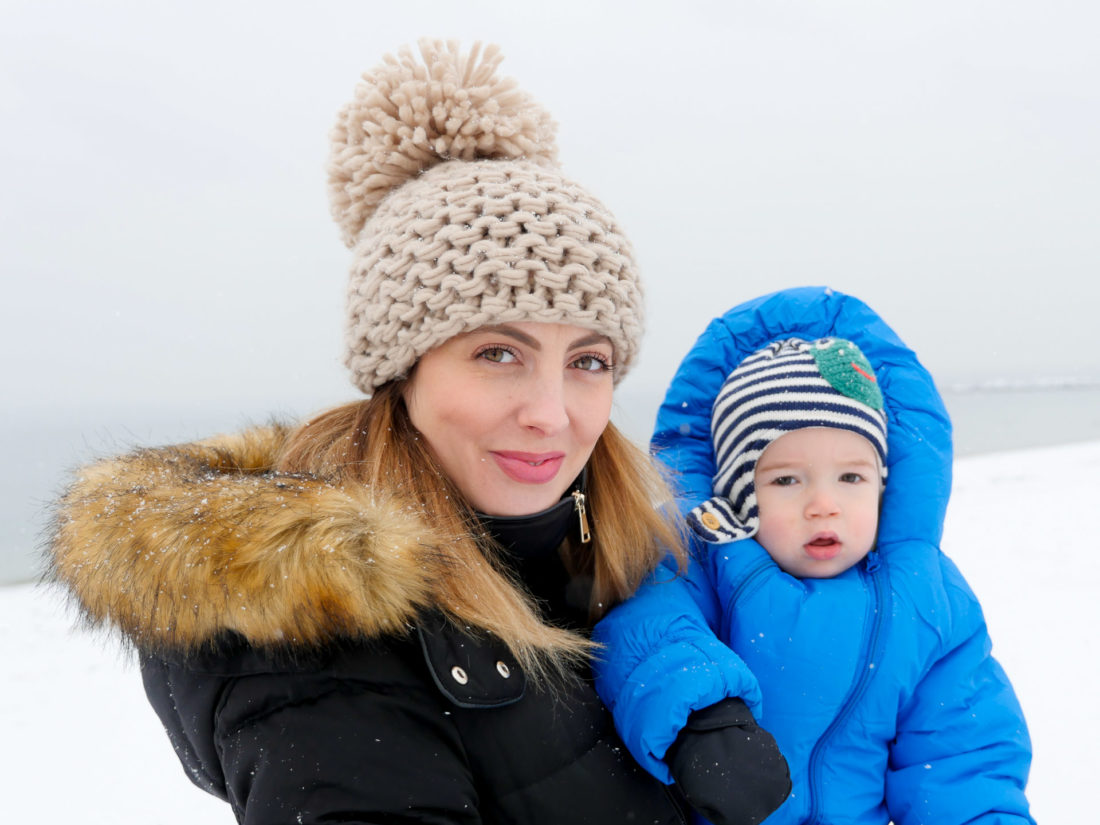 Eva Amurri Martino wears a tan knit beanie and faux fur lined parka, and holds one year old son Major on the snowy beach in Westport, CT