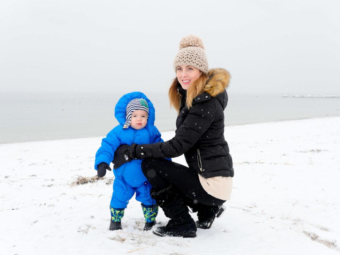 Eva AMurri Martino holds son, Major, in a snowsuit on the snowy beach in Westport, CT