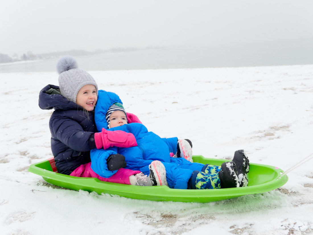 Marlowe Martino holds little brother Major in snowsuits on a green sled on the snowy beach in Westport, CT