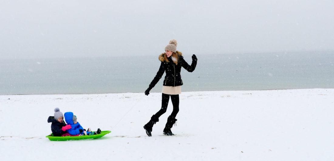 Eva Amurri Martino pulls her children through the snow on the beach in Westport, CT