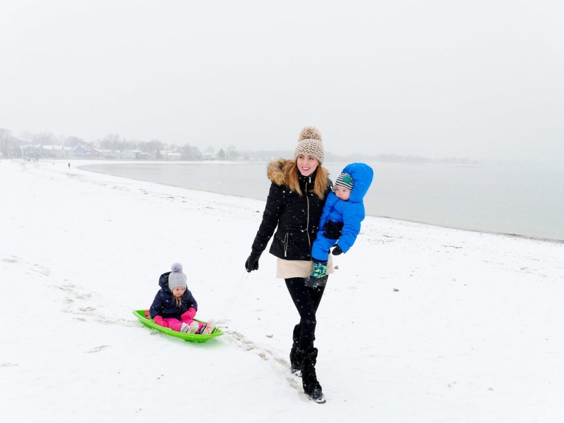 Eva Amurri Martino carries her one year old son, and pulls her three year old daughter through the snow on the beach in Westport, CT