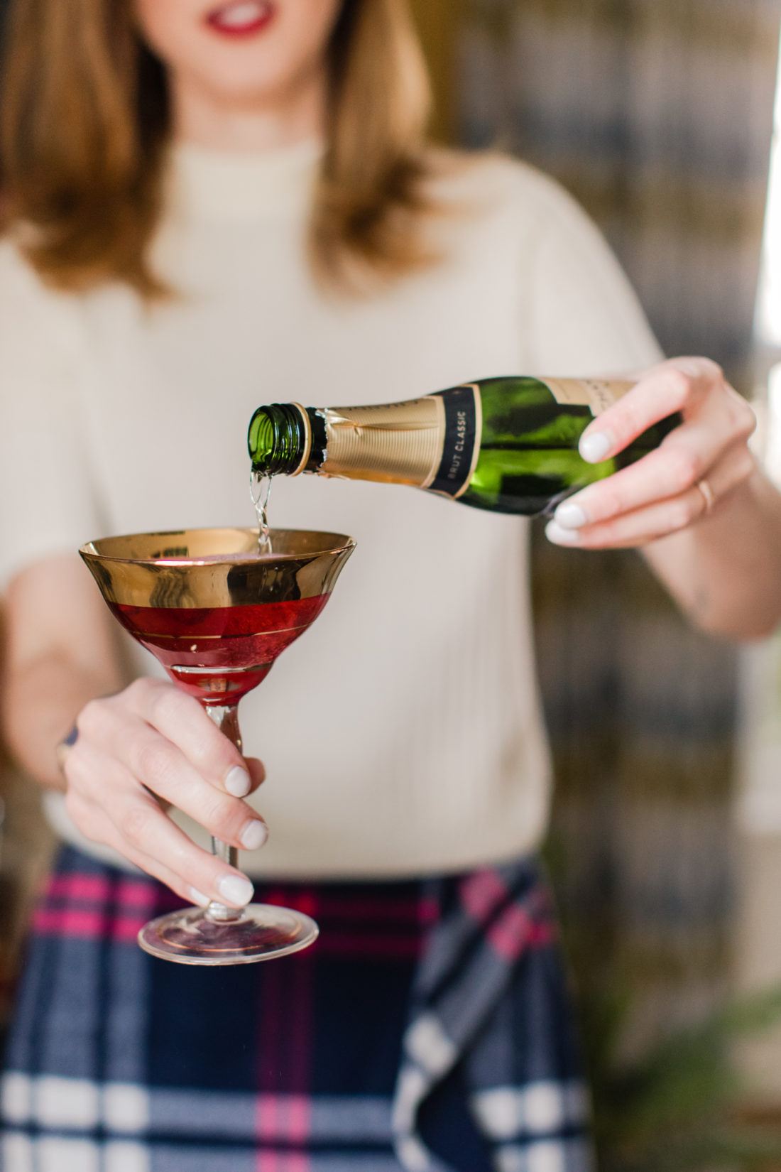 Eva Amurri Martino pours champagne in to a poinsettia cocktail in the living room of her Connecticut home