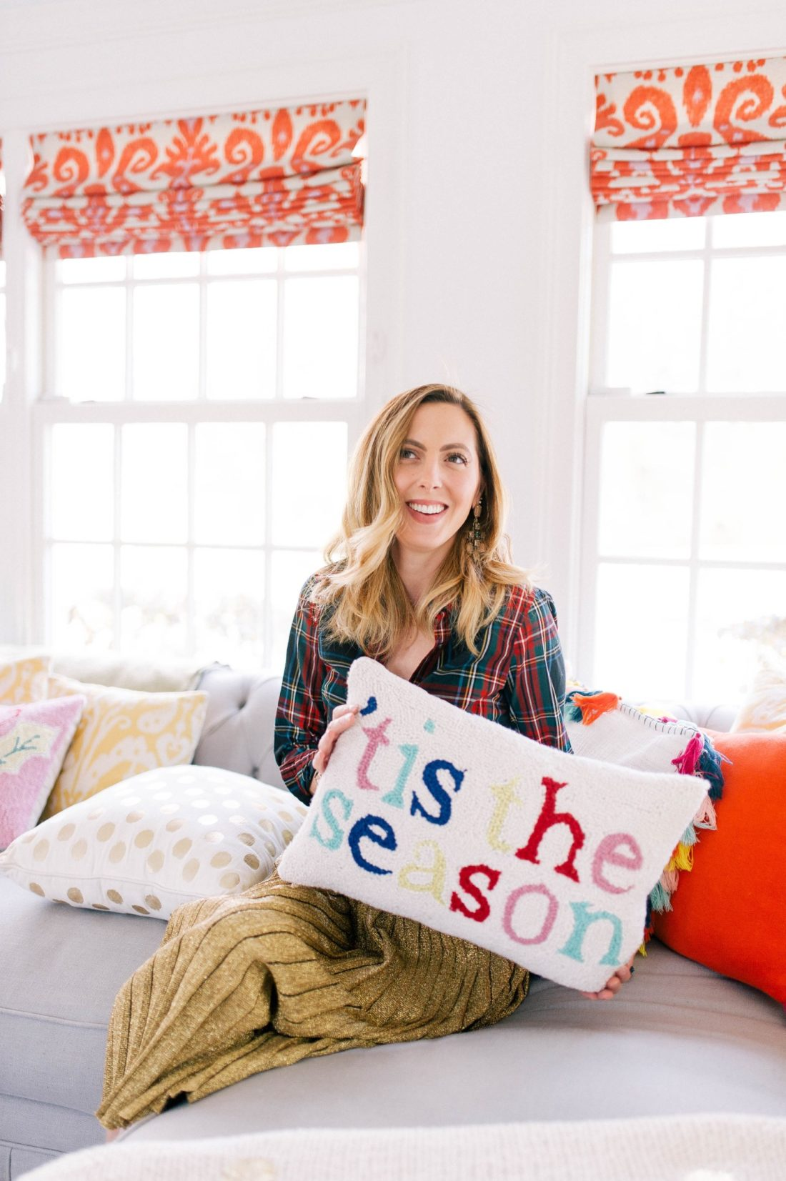 Eva Amurri Martino wears a plaid shirt and gold skirt and holds a festive Christmas pillow in the family room of her Connecticut home