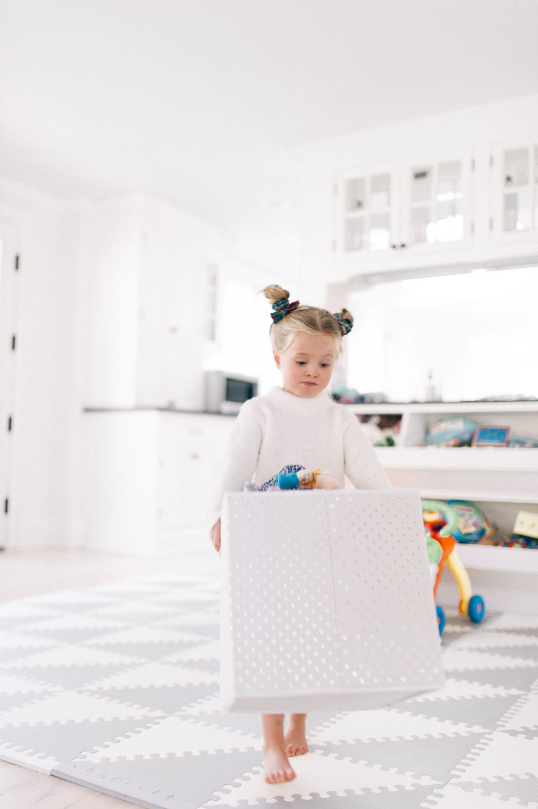 Marlowe Martino carries a box of toys to donate to children in need at Christmas Time