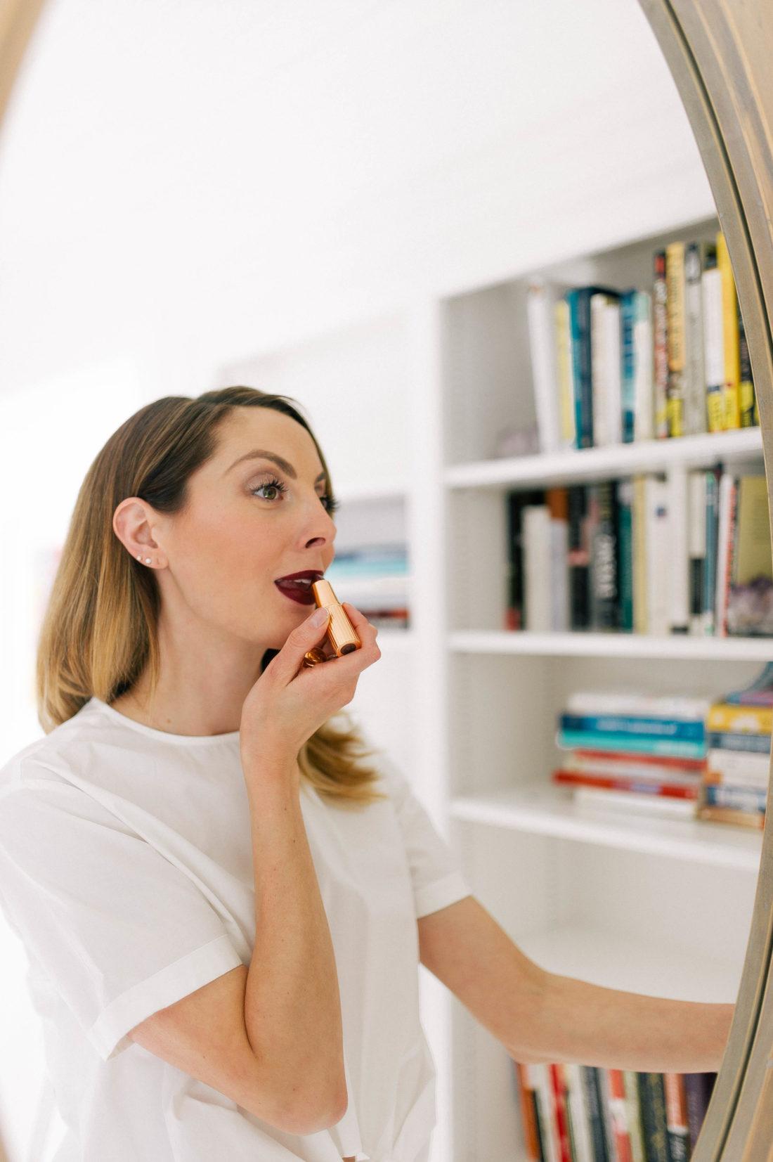 Eva Amurri Martino applies a deep red shade of lipstick