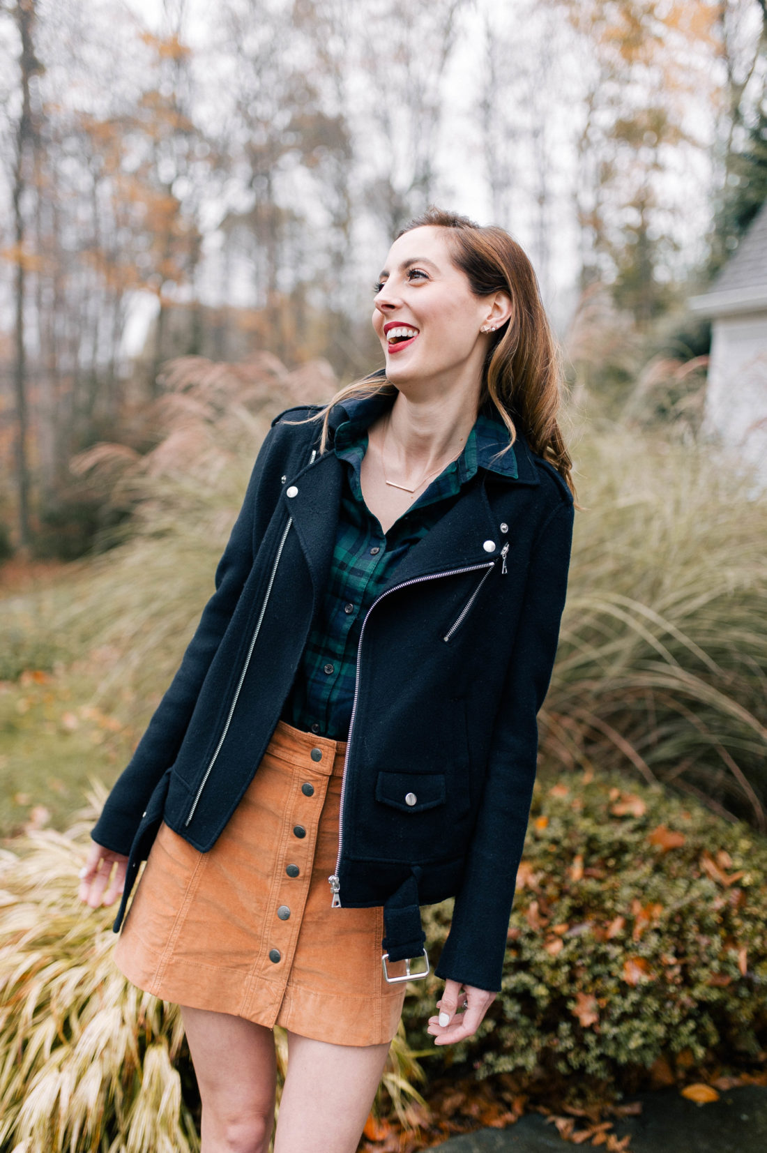 Eva Amurri Martino wears a plaid shirt, velvet button skirt, and blue motorcycle jacket on the pathway outside her Connecticut home