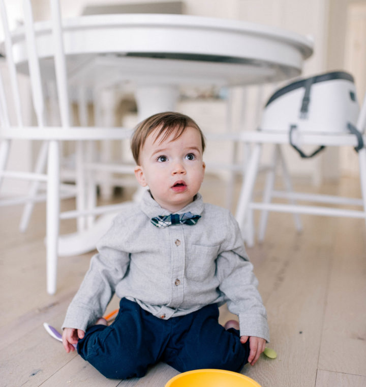 Major Martino wears a grey flannel button down shirt and tartan bow tie, and sits on the kitchen floor in his Connecticut home