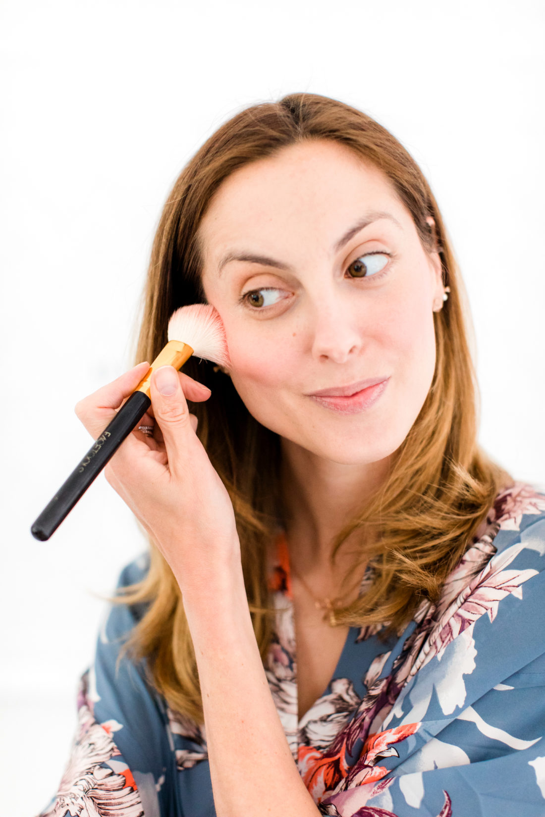Eva Amurri Martino applies blush to the apples of her cheeks and cheekbones as part of her photo shoot beauty tutorial