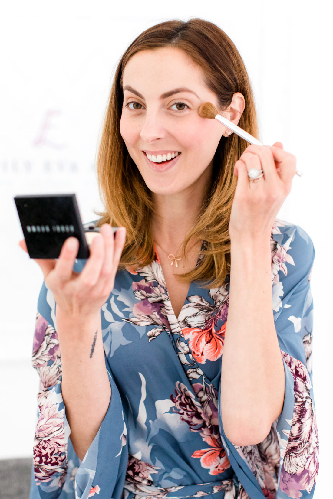 Eva Amurri Martino applies translucent powder to her skin over her foundation and concealer as part of her makeup tutorial