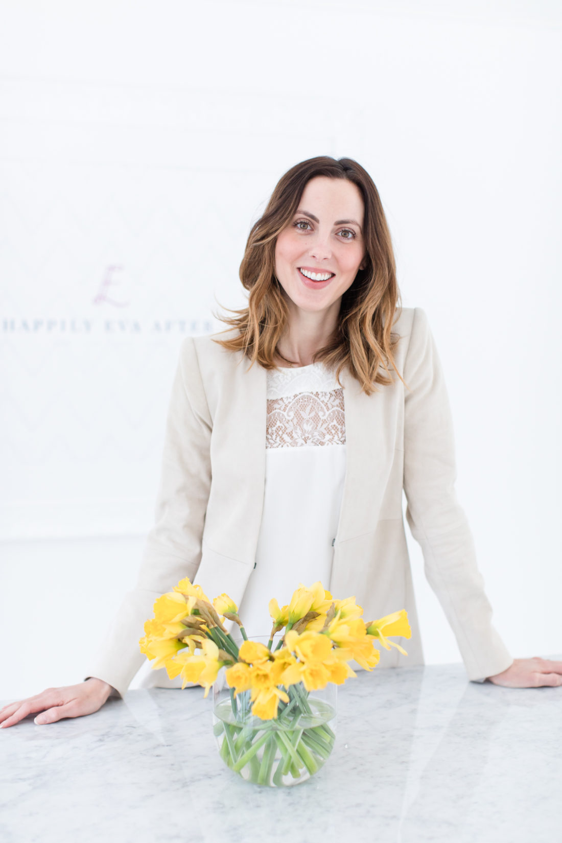 Eva Amurri Martino wears a white camisole top and tan blazer, and stands in the happily eva after studio with a bowl of daffodils