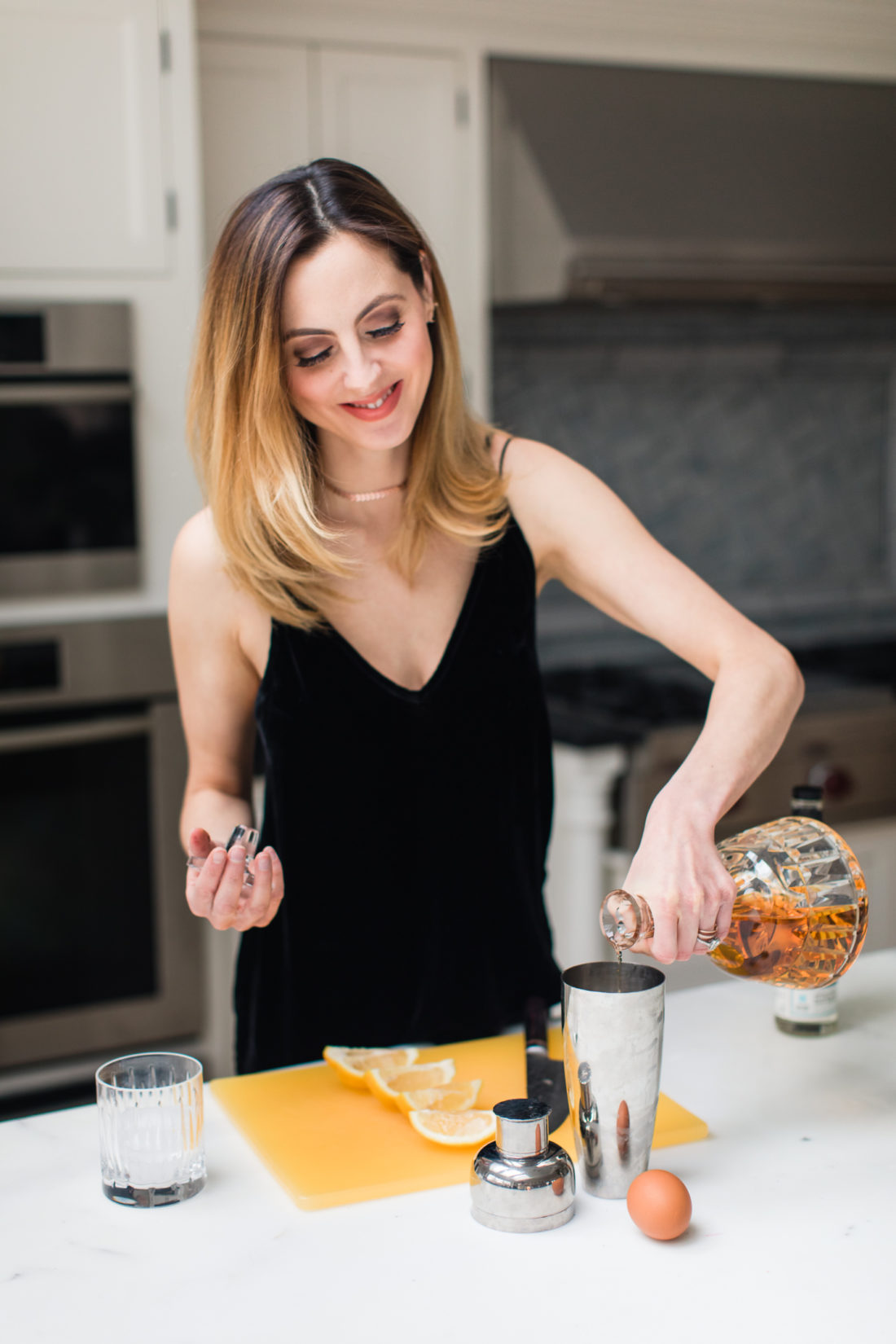 Eva Amurri Martino wears a black velvet spaghetti strap top and mixes up a whiskey sour in the kitchen of her Connecticut home