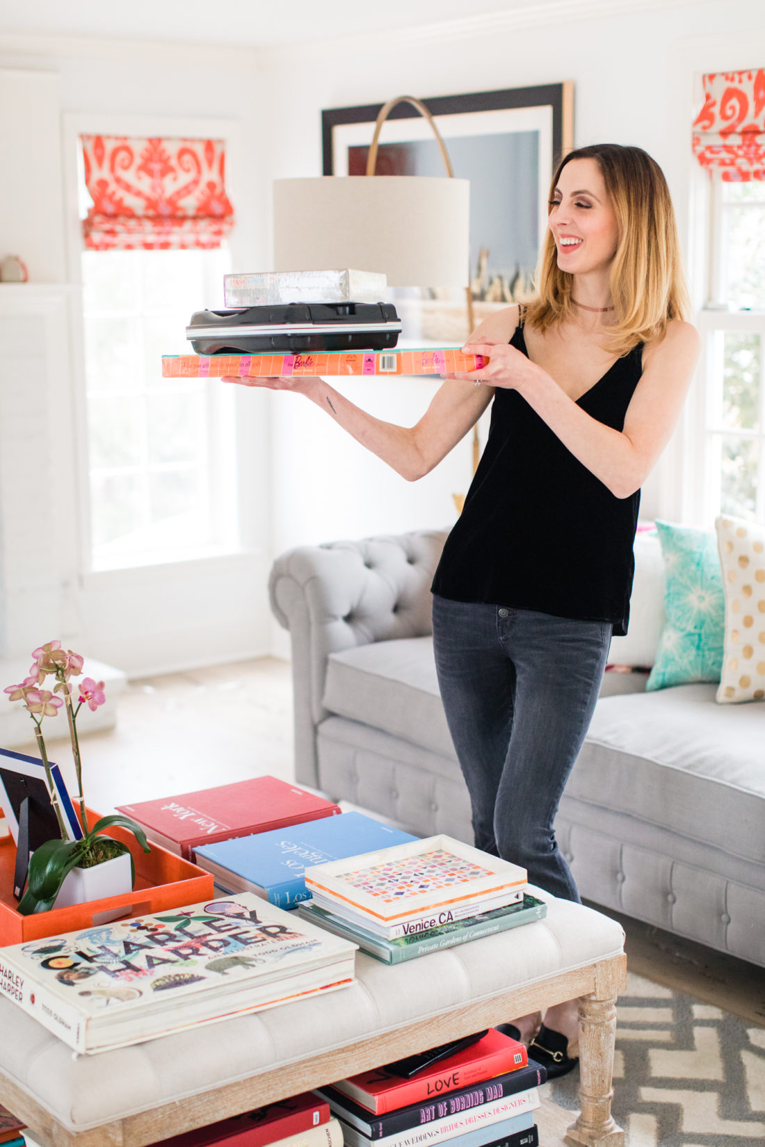 Eva Amurri Martino carries a selection of board games in to the family room to set up for a date night at home