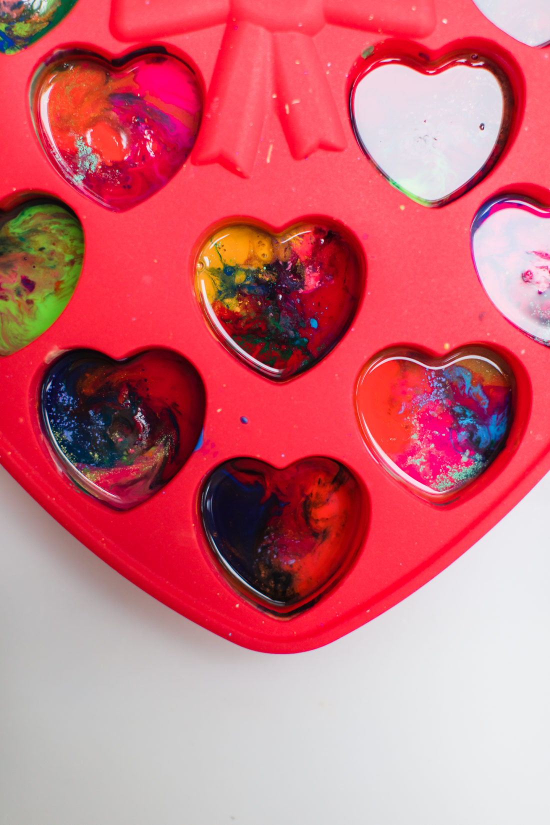 Melted crayon bits in a heart shaped mold for Valentine's Day favors