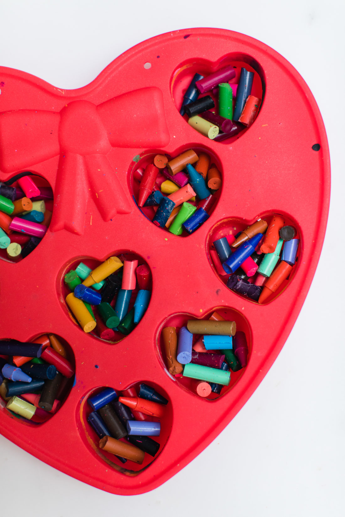 Broken bits of crayons in a heart mold are prepared to be made in to crayon hearts for Valentine's Day