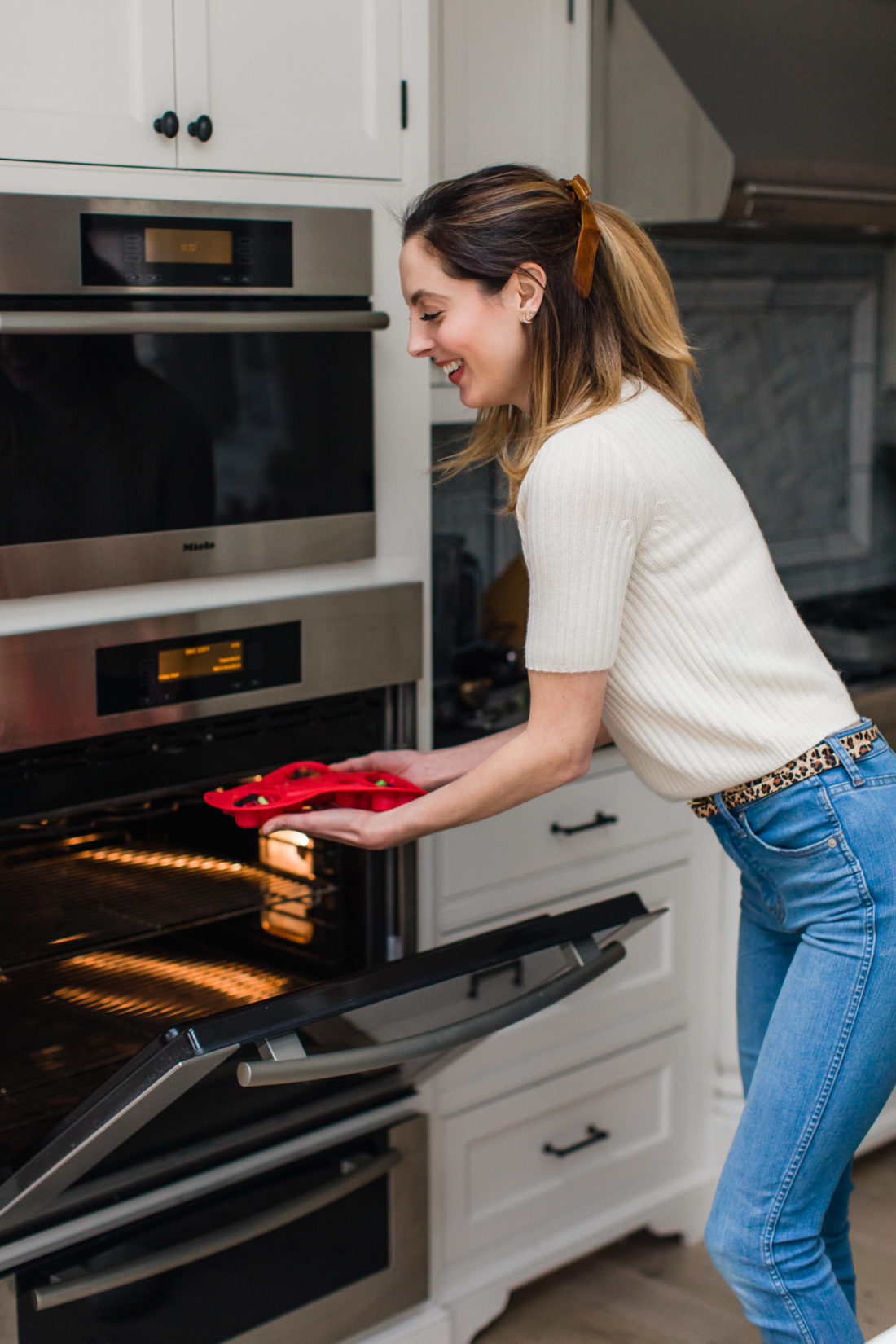 Eva Amurri Martino wears jeans and white sweater top and puts a heart shaped mold of crayons in to the oven