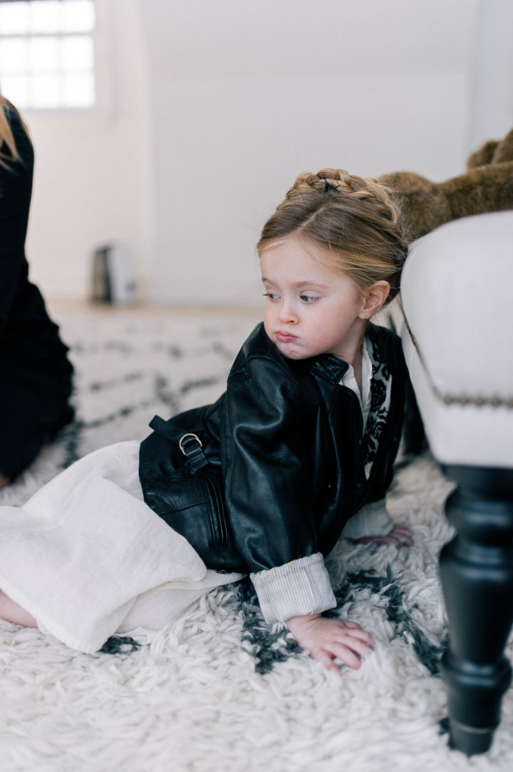 Marlowe Mae Martino makes a pouty face wearing a leather jacket with a halo braid in her hair while lying on the rug in her parents bedroom in Connecticut.