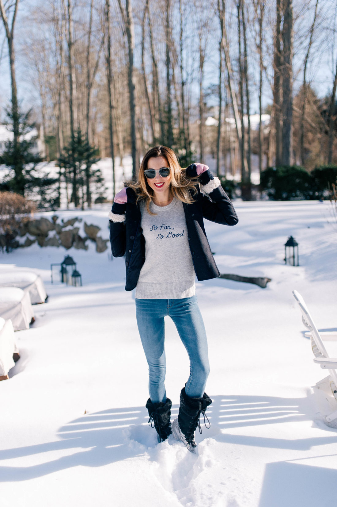 Eva Amurri Martino wears old navy jeans, black snow boots, a grey sweater and pea coat and stands in the snow outside her Connecticut home
