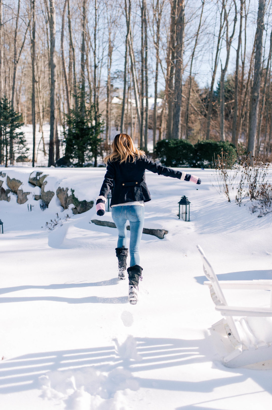 Eva Amurri Martino jumps through the snow outside her Connecticut home while wearing black furry snow boots