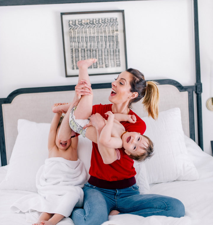 Eva Amurri Martino wears a red sweater and jeans, and lifts one year old son, Major, in the air to tickle him