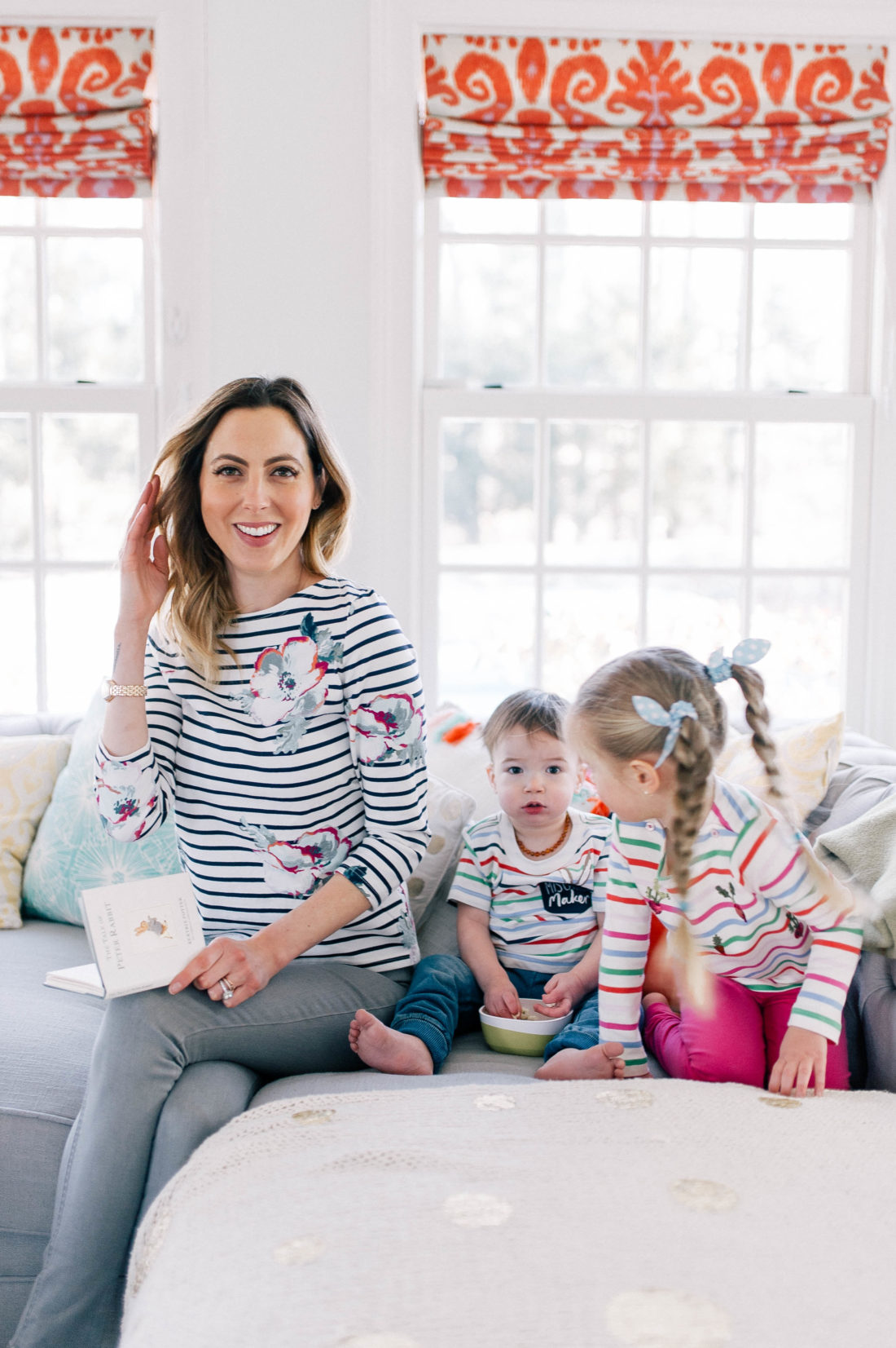 Eva Amurri Martino wears stripes and reads the Peter RAbbit book to her children on the couch at home in Connecticut