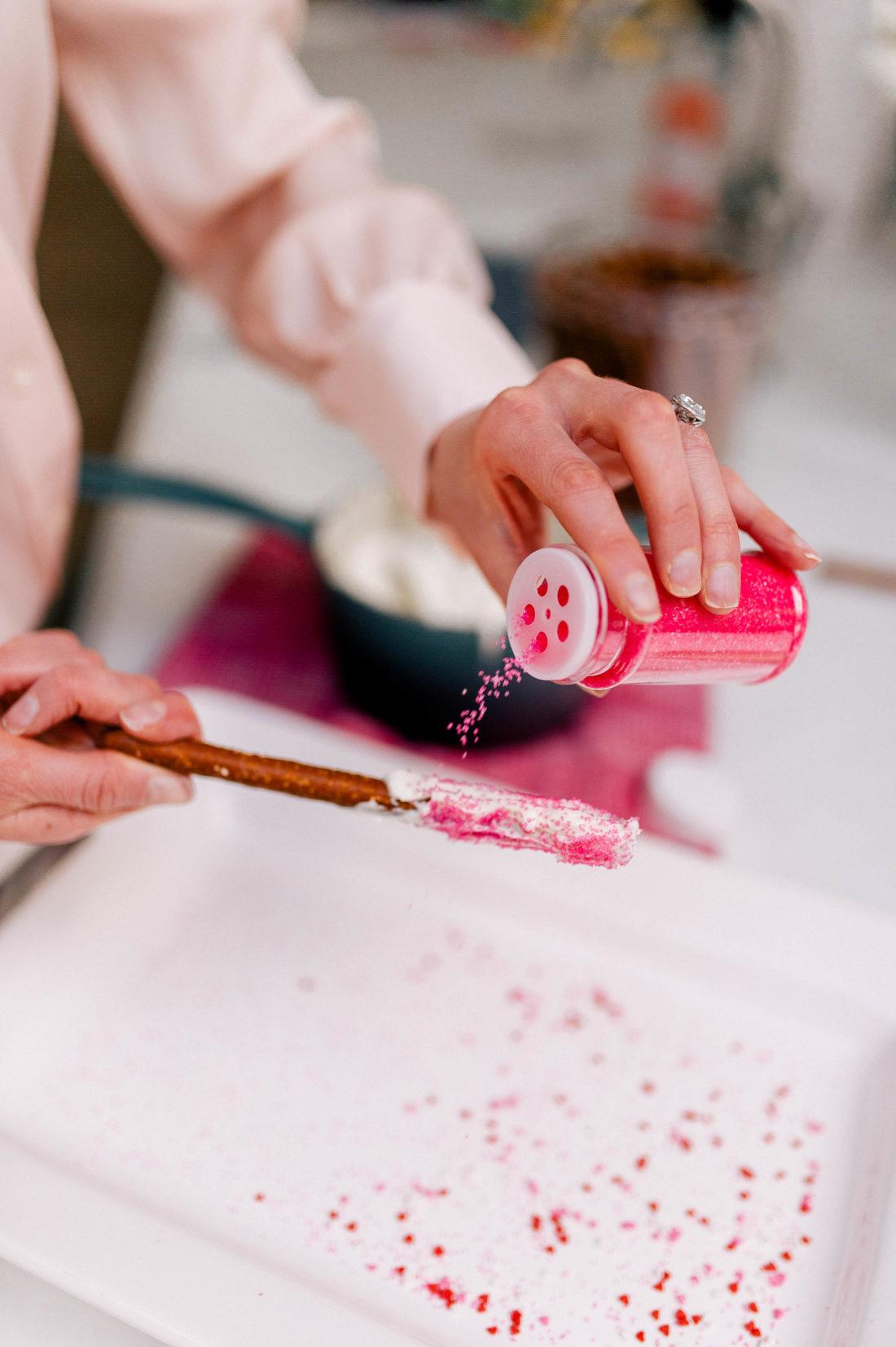 Eva Amurri Martino sprinkles ted sprinkles on a chocolate covered pretzel rod
