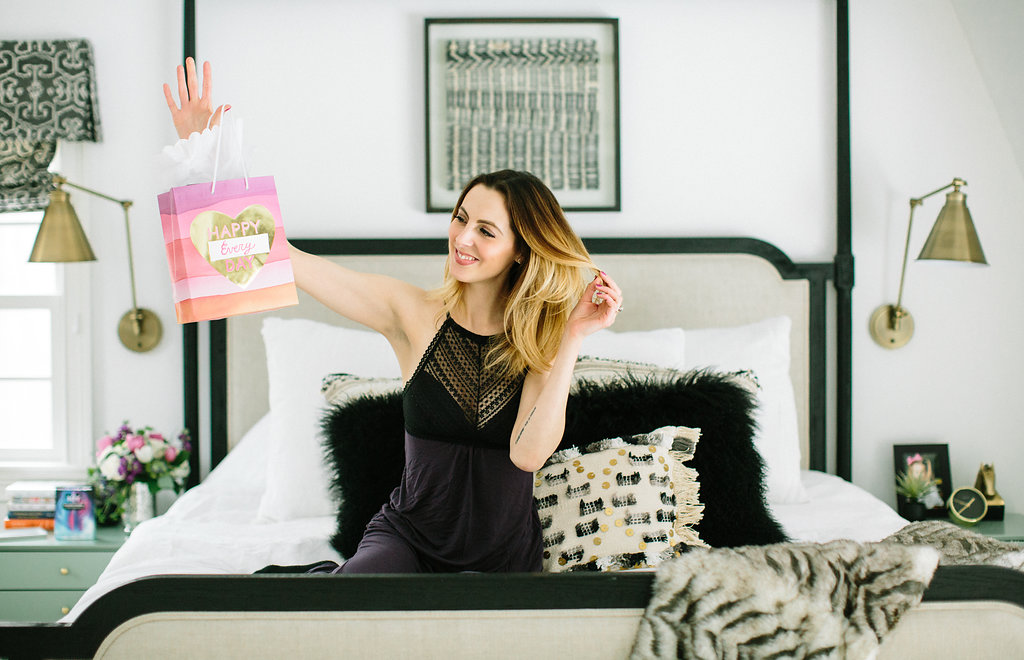 Eva Amurri Martino wears a pair of lacy pajamas and holds a Valentine's Day gift bag on the bed of her Connecticut home