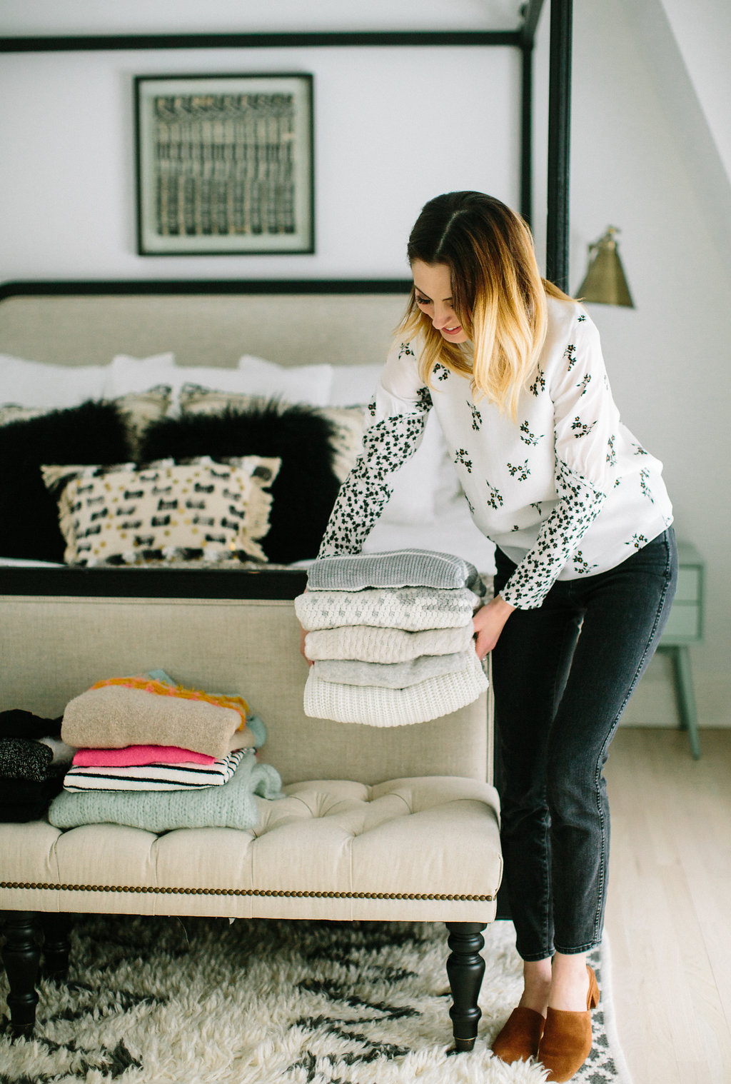 Eva Amurri Martino makes stacks of sweaters on the bed at the foot of her master bed